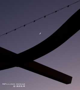 Denner's distinct architecture frames a recent crescent moon.